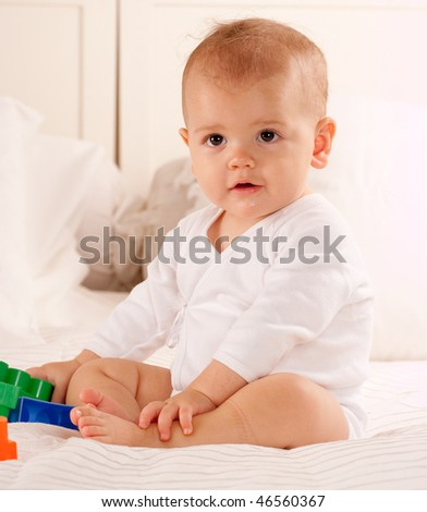 Cute baby on a white bed playing with colourful toy bricks - stock photo