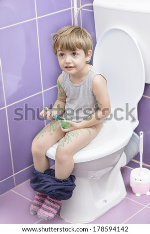 Cute baby on toilet drawing himself - stock photo
