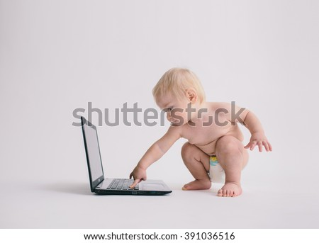 Cute baby playing with a laptop computer isolated on white - stock photo