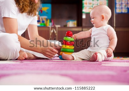 Cute baby playing with her mother on pink carpet - stock photo