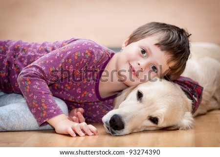 Cute baby playing with his dog - stock photo