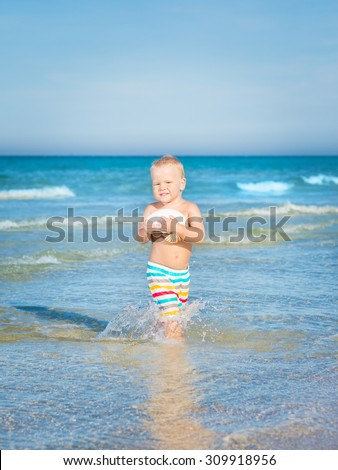 Cute baby plays in a sea - stock photo