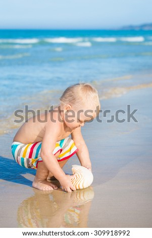 Cute baby plays in a sea