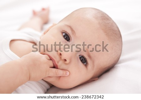 Cute baby putting fingers in to mouth - stock photo