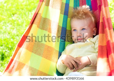 cute baby resting on a colorful hammock Beautiful cheerful little boy resting in a hammock and having fun. Positive emotions. - stock photo