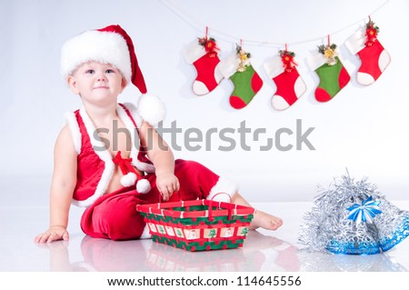 Cute baby Santa Claus with garlands and Christmas basket - stock photo
