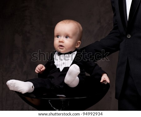 Cute baby sitting on chair. - stock photo