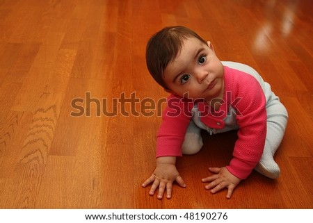 Cute baby sitting on hardwood floor - stock photo