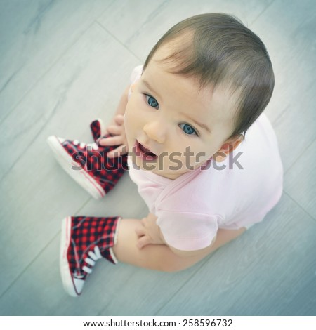 Cute baby sitting on the floor and looking at camera. Child is wearing in red sneakers. Top view. - stock photo