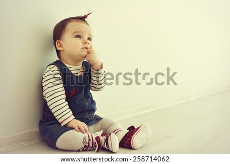 Cute baby sitting on the floor near the wall and thinking. The girl is looking up. You can use this photo for Idea concept. - stock photo
