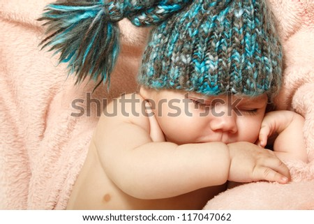 cute baby sleeping on pink plaid in funny hat, beautiful kid's face closeup with copyspace - stock photo