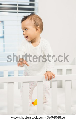 Cute baby standing in the crib in bedroom - stock photo