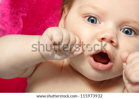 cute baby surprised, beautiful kid's face and hands closeup, studio shot