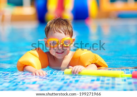cute baby swimming in pool with inflatable arm rings - stock photo