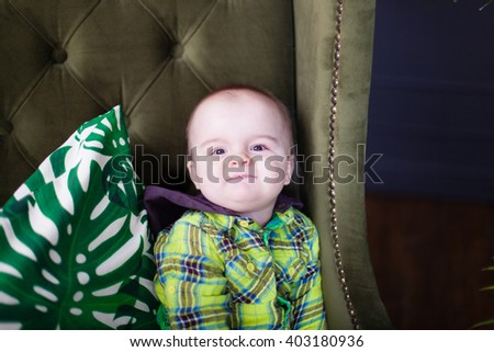 Cute baby toddler sitting on a green armchair near white checkered pillow, fool around, smile - stock photo