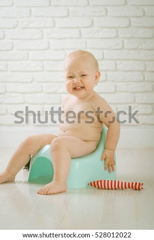 Cute baby training to piss into pot