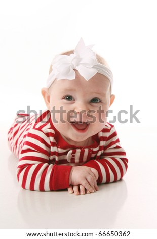 Cute baby wearing Christmas pajamas lying on tummy, isolated on white