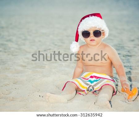Cute baby wearing Santa hat on the beach - stock photo