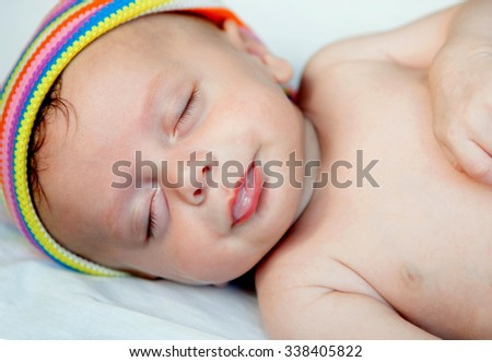 Cute baby while sleeping with a colored headscarf - stock photo