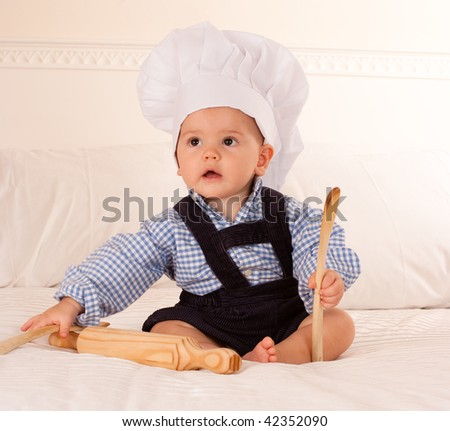 Cute baby with a cook hat playing with a rolling pin and wooden spoons - stock photo