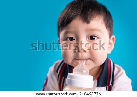 Cute baby with a milk bottle on blue background - stock photo