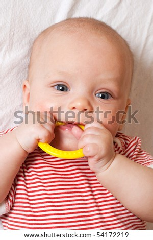 Cute baby with a yellow teething ring - stock photo