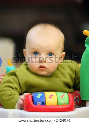 Cute baby with blue eyes playing in his walker - stock photo