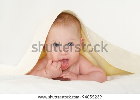 cute baby with blue eyes under towel