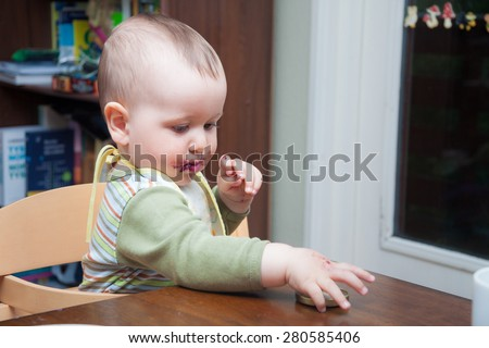Cute baby with mouth stained with blueberry jam playing with the cap of the jar