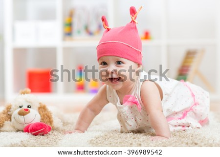 cute baby with toy crawling on the floor - stock photo