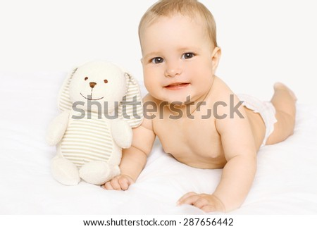 Cute baby with toy lying on the bed at home