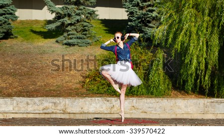 Cute ballerina dancing hipster in autumn park. Girl listening to music on headphones. A girl wearing a tutu and sneakers, sunglasses. Girl dancing ballet pas on tiptoe. The concept of youth fashion. - stock photo