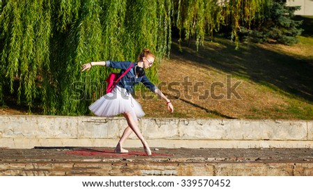Cute ballerina dancing hipster in autumn park. Girl listening to music on headphones. A girl wearing a tutu and sneakers, sunglasses. Girl dancing ballet pas. The concept of youth fashion. - stock photo