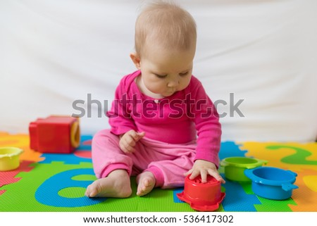 Cute bare feet  baby girl in pink clothes sitting on colorful puzzle play mat and playing with toys.