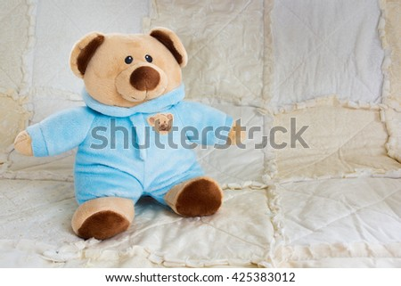 Cute Bear Stuffed Animal on a White Quilt - stock photo