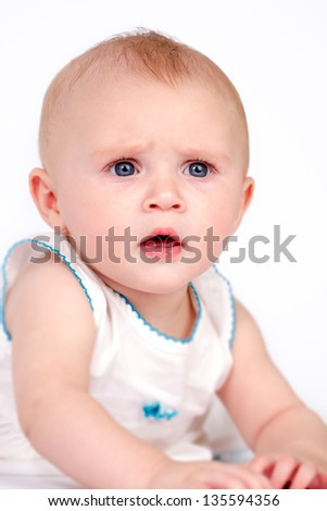 cute beautiful blue eyed baby girl frowning isolated on white