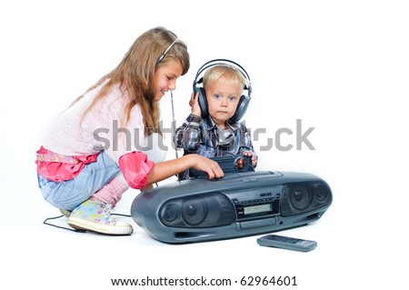 Cute beautiful brother and sister listen to music on headphones. In the studio - stock photo