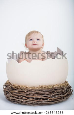 cute beautiful emotional baby sitting in easter egg with nest  on white background - stock photo