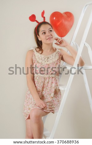 cute beautiful girl dreaming about Valentine's day on stairs, happy holiday concept