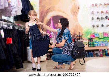 Cute beautiful little girl with her mother to buy clothes in shop