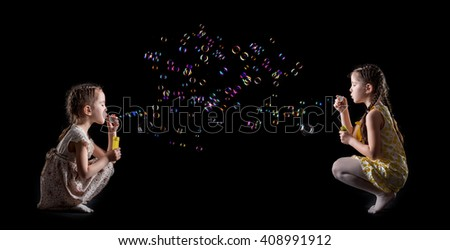 cute beautiful little girls and soap bubbles . happy children. girls blow soap bubbles on a black background. two sisters - stock photo