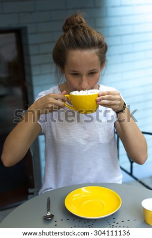 cute beautiful lonely teenager girl drinking hot cocoa with homemade marshmallows in cafe sitting outside - stock photo