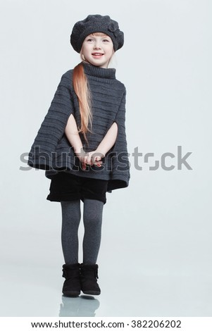 Cute beautiful red haired little girl posing in  the studio.