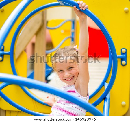 cute beautiful smiling little girl on a playground - stock photo
