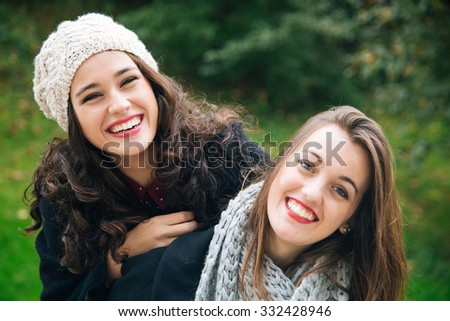 Cute best friend girls a piggyback in winter or fall outdoors - stock photo