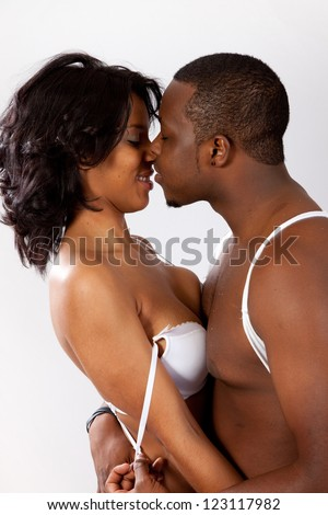 cute black couple kissing, man and woman in romantic play with passion and love - stock photo