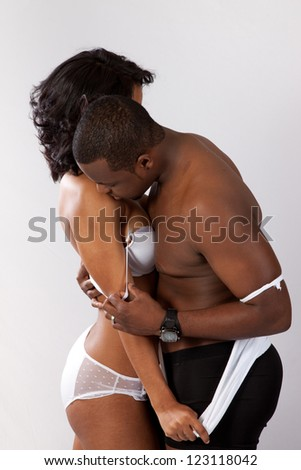 cute black couple kissing, man and woman in romantic play with passion and love; he is removing her bra and she is tearing his shirt off - stock photo