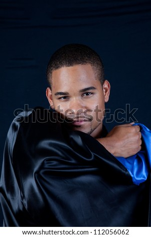 Cute black man with a black cape, looking at the camera over the shiny material - stock photo