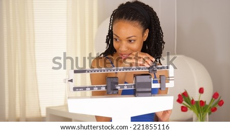 Cute black woman dancing on scales - stock photo