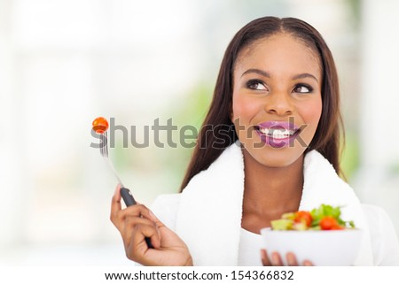 cute black woman eating vegetable salad at home - stock photo